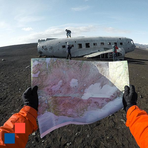 Un aventurier perdu ouvre un plan devant une carcasse d'avion dans le désert